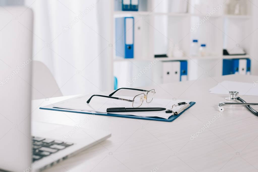 glasses and pen on clipboard on working table in clinic