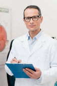 Fotografia Ritratto del medico con il blocco note in mani che guarda lobbiettivo in clinica