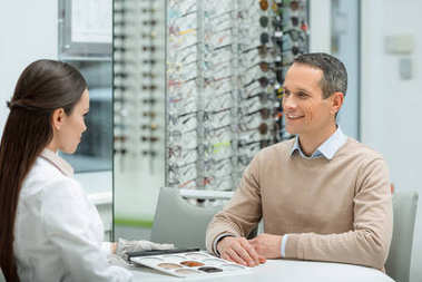 side view of smiling man looking at oculist while sitting at table in optics
