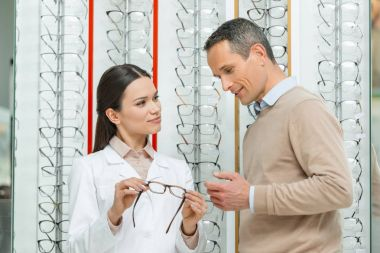 Oculist helping man to choose pair of eyeglasses in optics stock vector