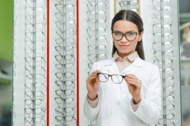 portrait of smiling optician in white coat holding pair of eyeglasses in optics