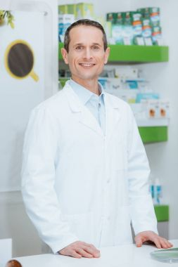 portrait of smiling optometrist in white coat standing at counter in optics
