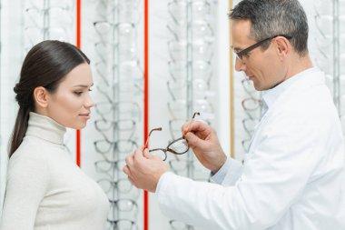 side view of oculist helping woman to choose pair of eyeglasses in optics