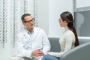 side view of ophthalmologist and young woman having conversation in optics