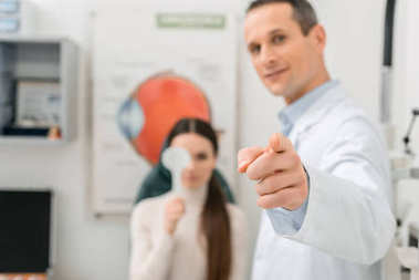 selective focus of patient getting eye test by oculist in clinic