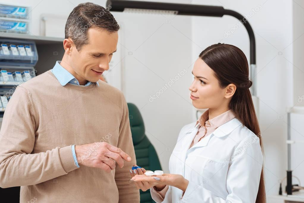 portrait of ophthalmologist show contact lens to patient in clinic