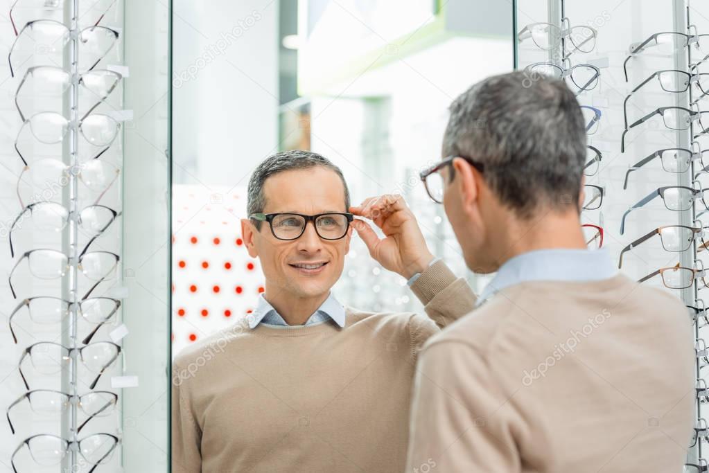 smiling caucasian man choosing pair of eyeglasses in optics