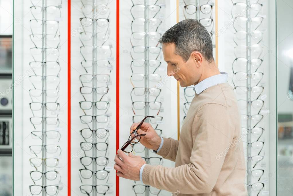 side view of caucasian man choosing pair of eyeglasses in optics