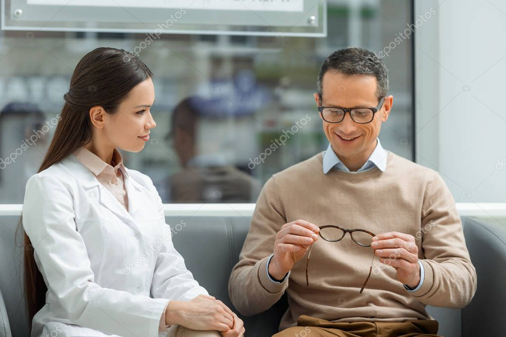 portrait of man looking at pair of eyeglasses in hands with ophthalmologist sitting near by