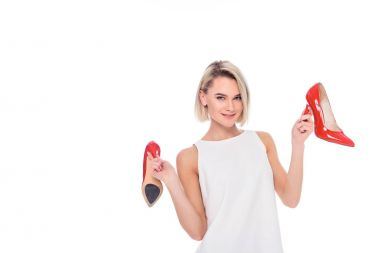 beautiful cheerful girl holding red heeled shoes, isolated on white