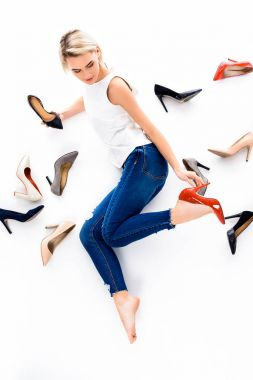 beautiful blonde woman posing with heeled shoes, isolated on white