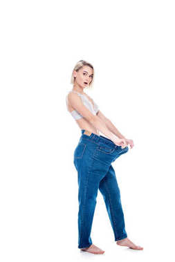 shocked girl showing weight loss by wearing old jeans, isolated on white