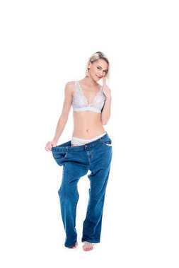 slim girl in old jeans old jeans after losing weight, isolated on white