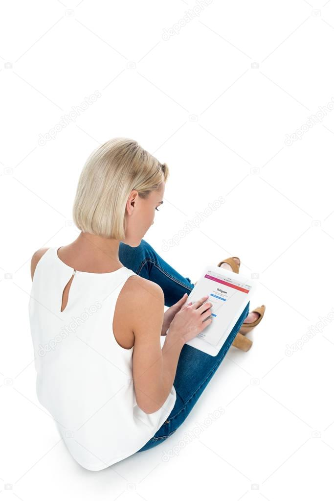 Back view of blonde woman using digital tablet with instagram app, isolated on white