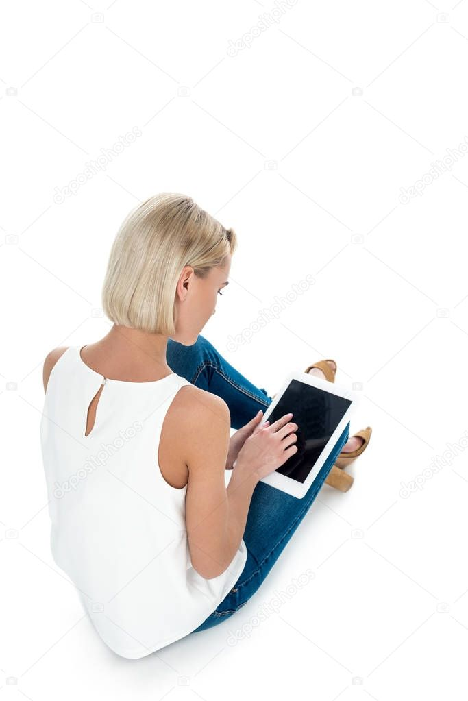 back view of blonde woman using digital tablet with blank screen, isolated on white