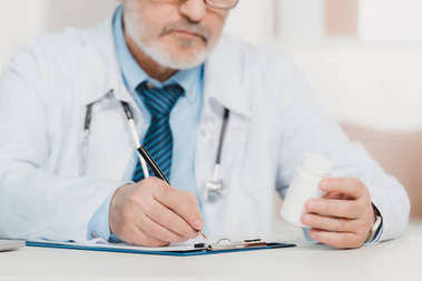 partial view of doctor with pills in hand making notes on notepad at workplace