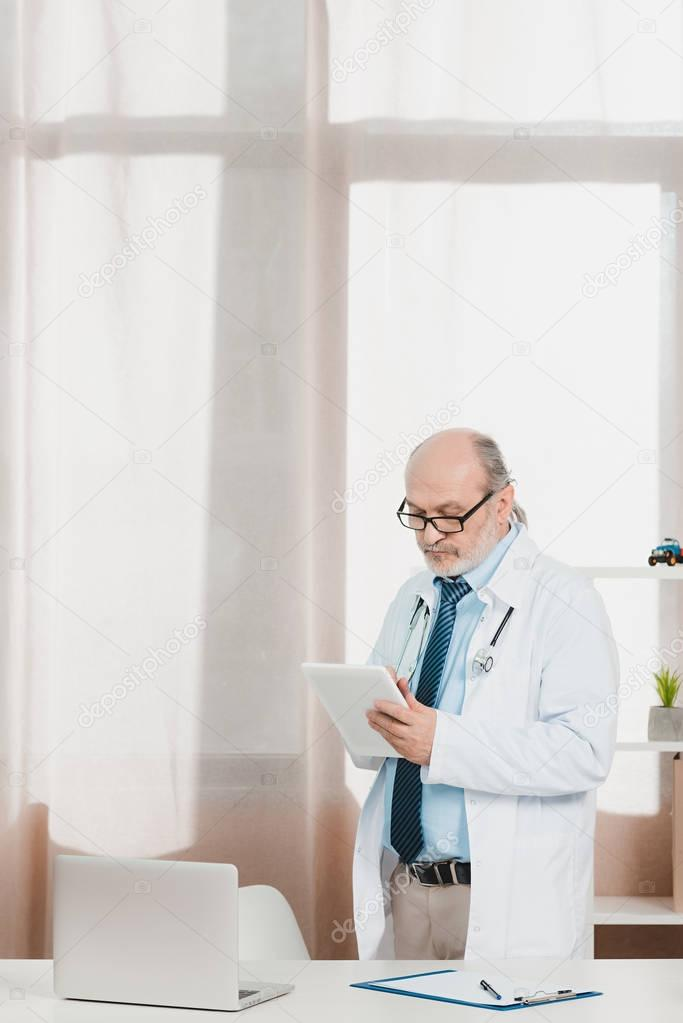 portrait of senior doctor in white coat with tablet in hands at workplace in clinic