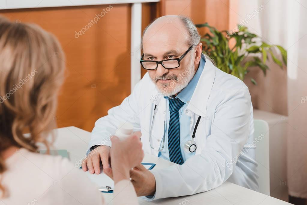 selective focus of senior doctor giving pills to patient in clinic