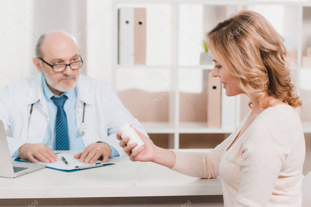 selective focus of smiling woman looking at pills in hand in clinic