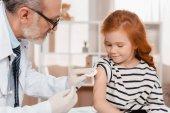 Arzt in medizinischen Handschuhen macht Spritze für kleines Mädchen in Klinik