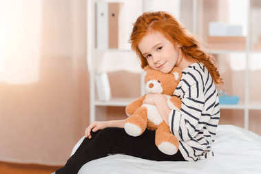 portrait of cute little girl with teddy bear looking at camera