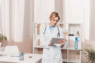 portrait of general practitioner in white coat using table in clinic