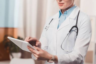 partial view of female doctor using tablet in hands in clinic
