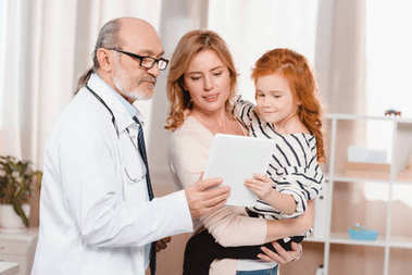 portrait of doctor in white coat, woman and daughter using tablet together in clinic