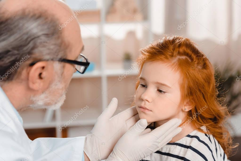senior pediatrician in medical gloves examining little patients throat in clinic