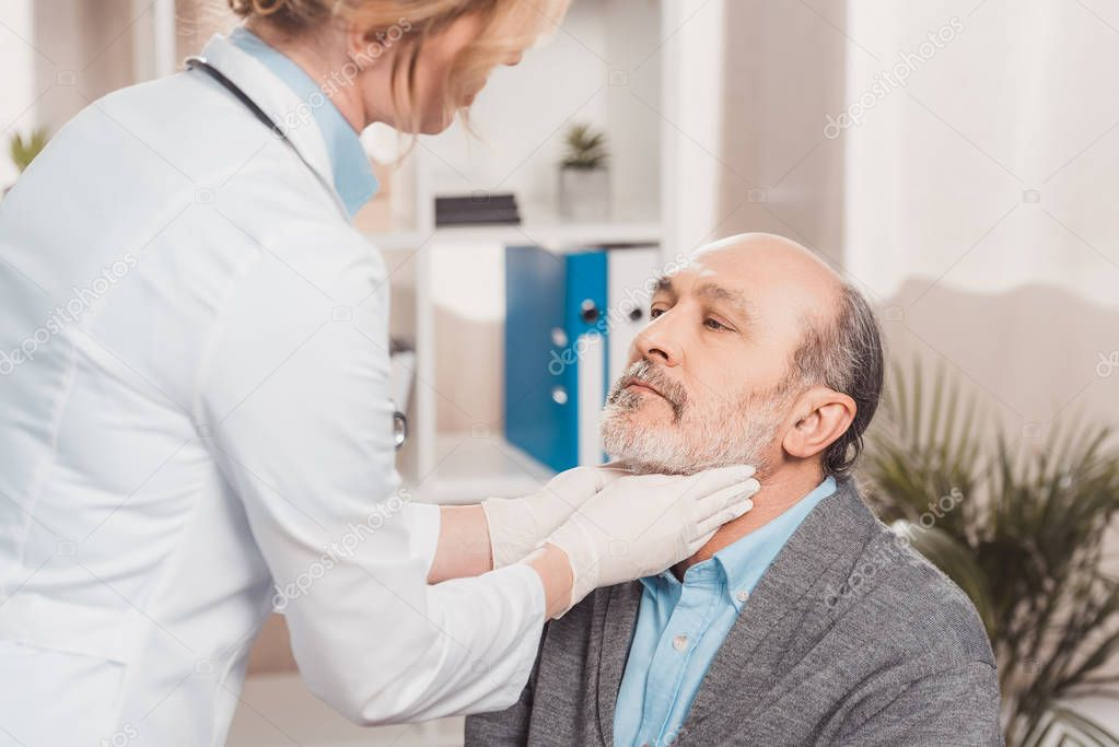 doctor in medical gloves checking patients throat in clinic