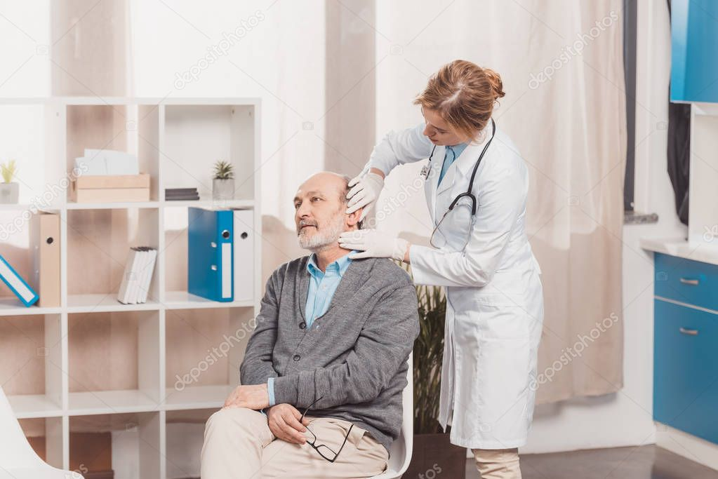 female doctor in medical gloves examining senior patient in clinic