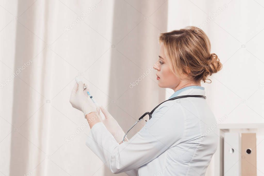 side view of doctor in white coat and medical gloves holding syringe for injection in hands in clinic