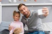 Fényképek csinos fiatal apa és lánya, teddy bear figyelembe selfie
