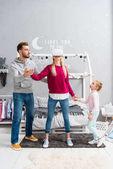Fotografia giovane famiglia felice che usando le cuffie da realtà virtuale in camera da letto bambino
