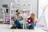 Fotografia genitori che esaminano la piccola figlia mentre lei usando le cuffie da realtà virtuale in camera da letto bambino