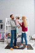 Fotografia genitori che trasportano piccola figlia mentre lei usando le cuffie da realtà virtuale in camera da letto bambino