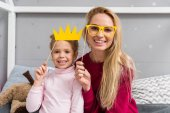 Fotografie smiling mother and daughter with toy masquerade crown and eyeglasses