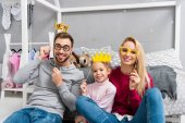 Fotografie happy young family with masquerade crowns and eyeglasses sitting in kid bedroom