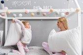 šťastný matka a dcera v pyžamu boj s polštáři