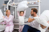 happy young family fighting with pillows in kid bedroom