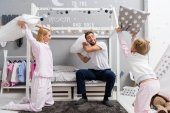 beautiful young family fighting with pillows in kid bedroom