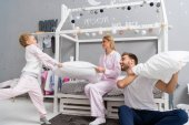 laughing young family fighting with pillows in kid bedroom