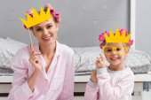 Fotografie smiling mother and daughter in pajamas with toy masquerade crowns