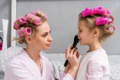 Fotografie young beautiful mother and daughter with hair rollers doing makeup