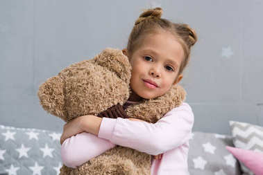 adorable little kid embracing her teddy bear and looking at camera