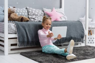 happy little kid sitting on floor and using tablet