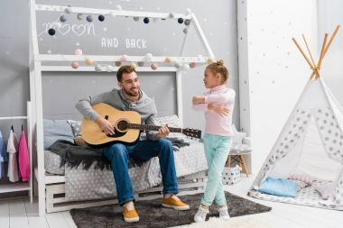 young father playing guitar for daughter in bedroom while she dancing in front of him