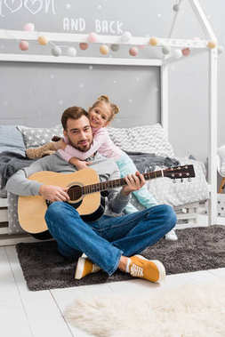 father playing guitar for daughter on floor of kid bedroom while she embracing him