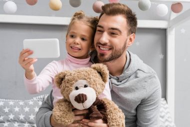 happy young father and daughter with teddy bear taking selfie
