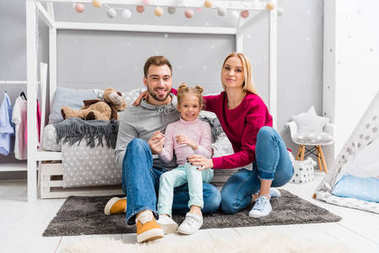 happy young family sitting on floor of kid bedroom together